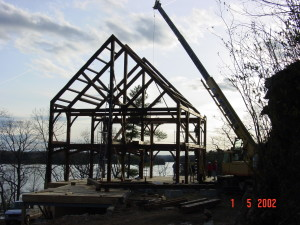 Timberframe being raised on a site.